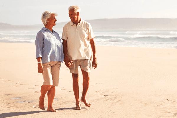 couple de retraité se baladant sur la plage