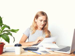 femme relisant ses factures devant son ordinateur